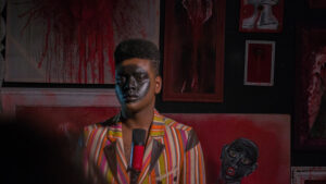 A Black person with a black circle painted on their face and wearing a colourful stripy jacket is in a room with red paint splattered on the walls and a microphone in front of them.