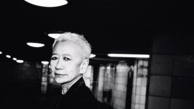 A black and white headshot of Shu Lea Cheang, a Taiwanese-American woman with short bleach blond hair, standing in a darkened corridor with bright overhead lights.