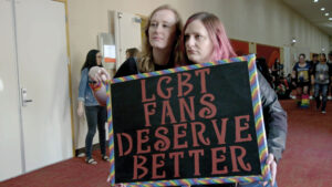 """Still from the film Queering the Script in which two white people standing in a hall at a fan convention hold up a sign which reads, """"LGBT fans deserve better."""""""