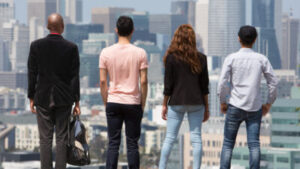 Four people stand with their backs to us, facing the city of San Francisco with tall buildings and blue sky in front of them.