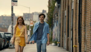 Two young people walking down a city street. One is a white woman wearing a yellow jumpsuit, and the other is a white man wearing a blue shirt and jeans. walking down a city street. They look purposeful and excited.