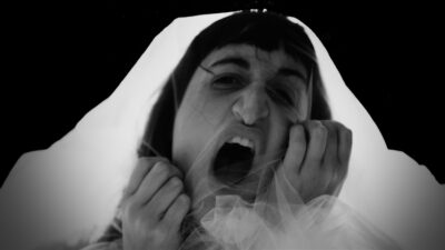 A close up black and white image of a person's face. They are clawing at a clear veil covering their face and have their mouth open like they are yelling. They look angry, desperate and fierce.