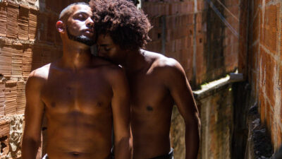 Two figures stand in half sunshine, half shade, against a bare brick and mortar wall outside. They are both topless, with one kissing the top of the other's shoulder. The kissed person has a trimmed beard and shaved head, and looks in a state of ecstasy. The kissing person has brown Afro-textured hair, partially bleached, looking enamoured.