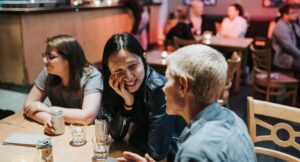three people sitting at a table in the CCA bar, with mellow lighting. A woman with long black hair sits smiling listening to a non binary person with short blonde hair talking. The third person is looking to the rest of the table. In the background others are talking at other tables. The mood is friendly and social.