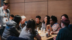 A group of people sit around a table in a bar laughing together.