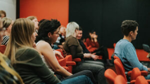 A group of people sitting in a brightly lit cinema chatting and looking towards the stage. In the foreground there is a person with long blond hair and a green jumper and a person with shorter black hair and a white vest. The atmosphere is warm and buzzing.