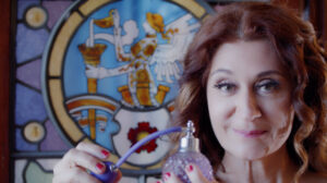A person with long, wavy auburn hair with highlights, with long eyelashes and pink lipstick, smiles at the camera, and is holding a beautiful vintage perfume bottle with a purple tassel. Behind them is a painted stained glass window, with a picture of a figure with wings and a hat holding a gold horn-like object with a ghost-like figure emerging from the object.