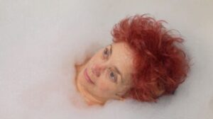 A white nonbinary person with red hair lying in the bath looking up at the ceiling. They are surrounded by bubbles. They look zoned out.