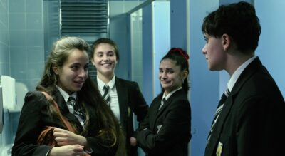 Three school girls stare at a boy with vicious smiles on their faces. One of the girls is tightly holding a brown school bag. They are in a school bathroom, and the boy looks worried and upset.