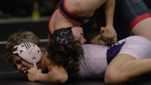 A close up of two white people wrestling. One is laying on top of the other, who is shouting. They both wear protective head gear and sports tunics. The image feels dynamic and active.
