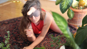 A person with long brown hair crawls on a persian-style rug in a room with wood-laminate floors, surrounded by green leafy potted plants. They are blindfolded, and have a dildo strapped to their forehead.