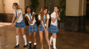 Four women of various races in a sexy plaid school uniform making gun shapes with their fingers. They are looking around cautiously as if they are looking for someone. The image feels fun and playful.