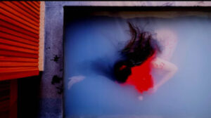 A person is submerged in a pool of milky water . The person looks in a state of undress, and has long black hair. Their face is covered by a thick, bright red liquid, which appears to be coming from their head and gathering around their body. To the left of the image is a red wood panelled wall.